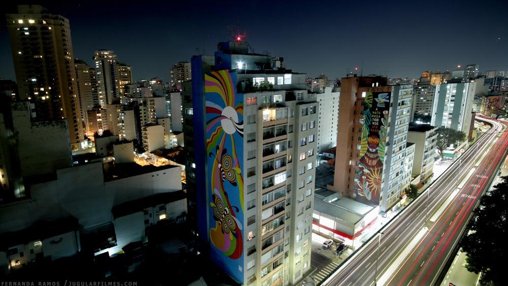 """Foto extraída do time-lapse que documentou a execução do grafite """"Metamorfose"""", de Marta Oliveira.. Mostra a emprena de um prédio com a pintura colorida."""